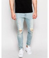 ASOS - Superenge Jeans mit zerschlissenen Knien in ausgeblichenem Blau - Blau